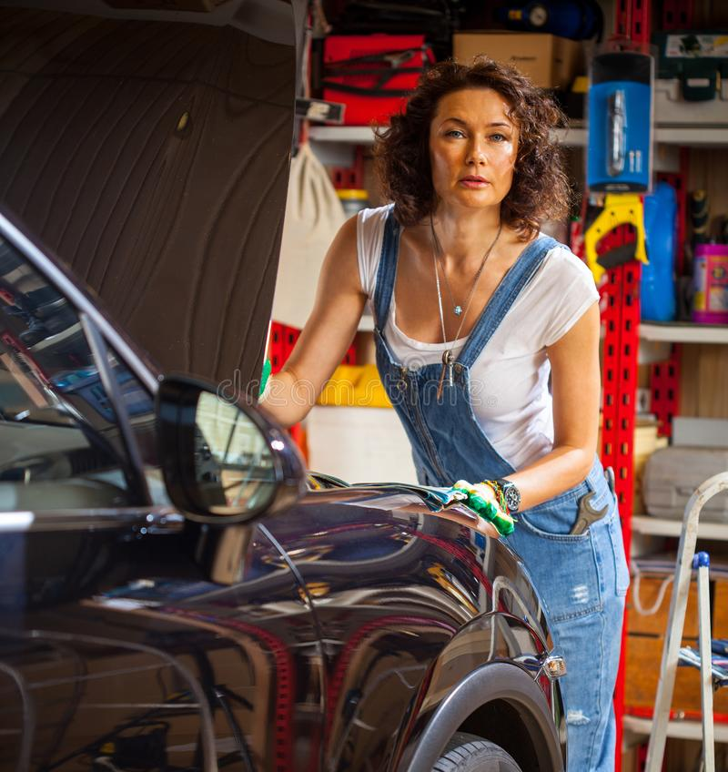 Woman auto mechanic in blue overalls royalty free stock image