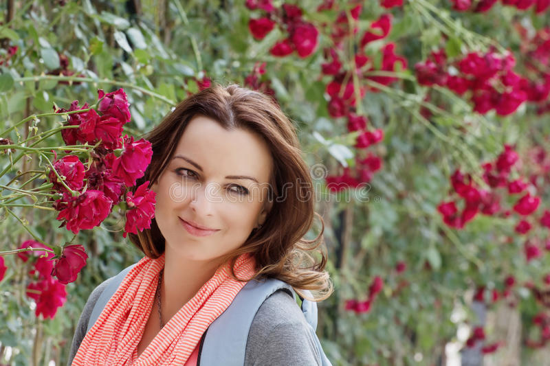 Beautiful woman in garden under red roses bower. Beautiful brunette in garden under red roses bower stock photography