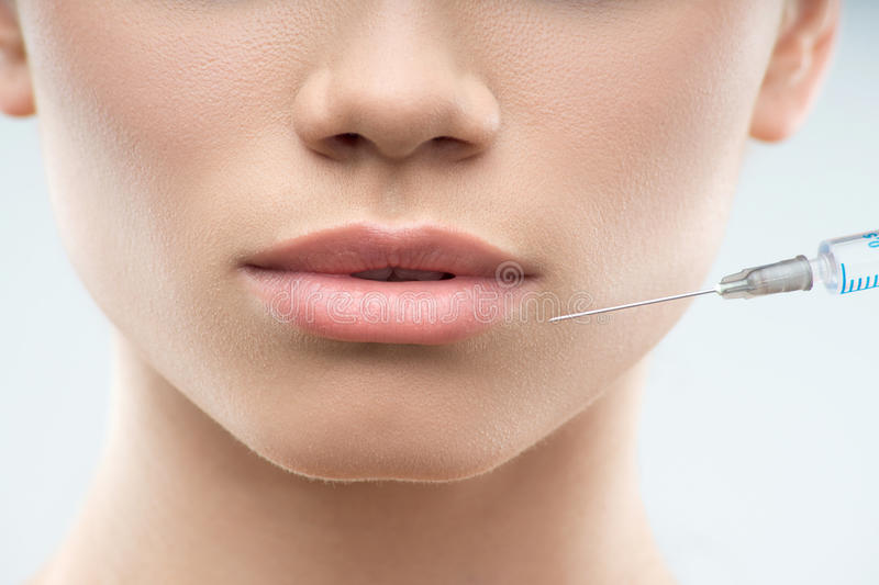 Beautiful woman gets injection in her face stock image