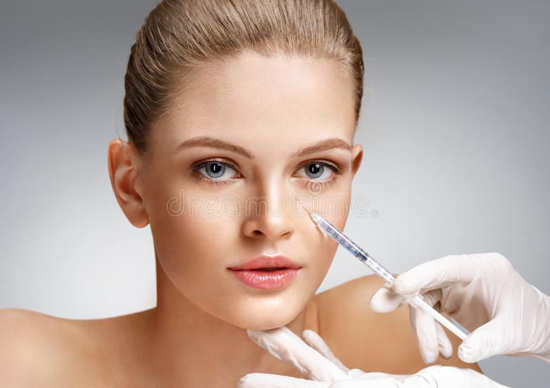 Beautiful woman getting cosmetic injection in eye area from beautician. stock images