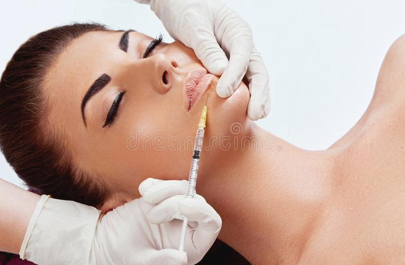Beautiful woman getting cosmetic injection in lips, Plastic surgery, beauty concept. stock photo