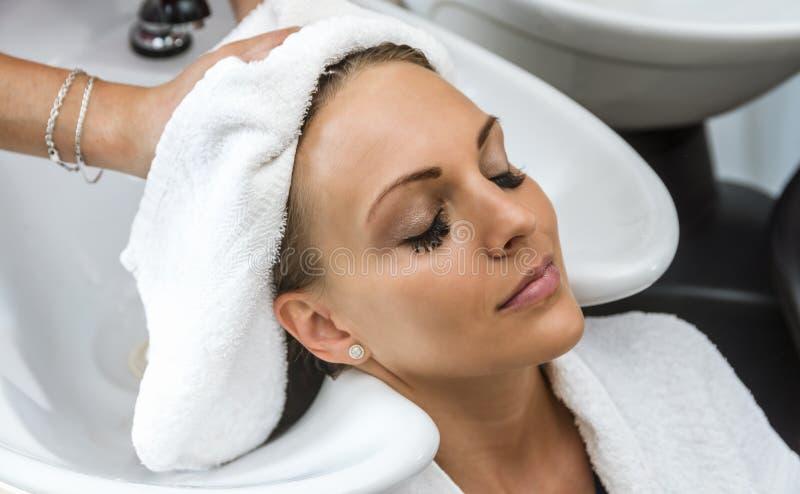 Beautiful woman getting hair wash in a hair salon royalty free stock photo