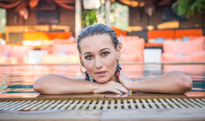 Beautiful woman getting out the pool royalty free stock photography