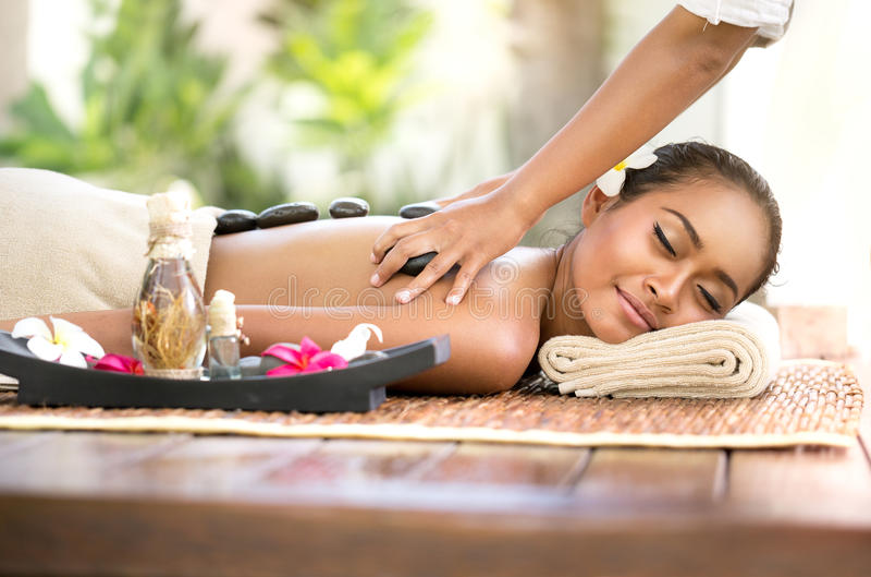 Beautiful woman getting spa hot stones massage in spa salon stock photography