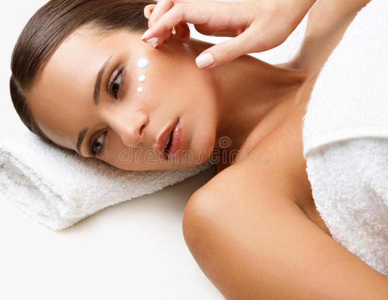 Beautiful Woman Getting Spa Treatment. Cosmetic Cream on a Cheek stock images