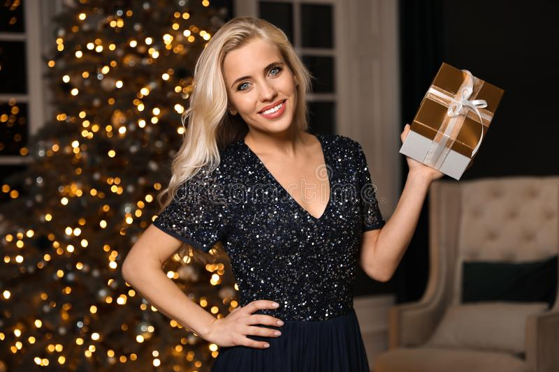 Beautiful woman with gift box in room. Christmas celebration. Beautiful woman with gift box in decorated room. Christmas celebration royalty free stock photos