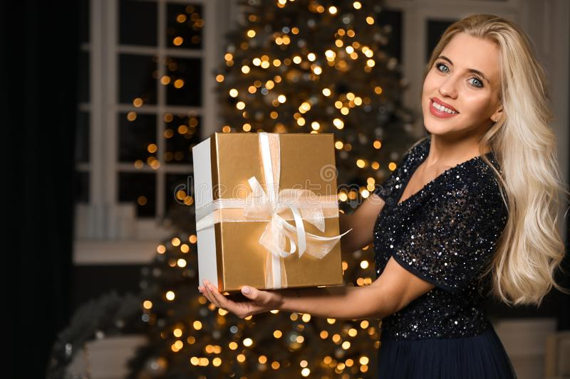Beautiful woman with gift box in room. Christmas celebration. Beautiful woman with gift box in decorated room. Christmas celebration stock images