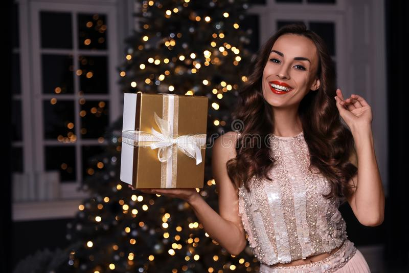 Beautiful woman with gift box in room. Christmas celebration. Beautiful woman with gift box in decorated room. Christmas celebration stock image