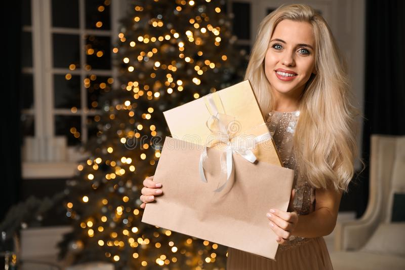 Beautiful woman with gift box and shopping bag in room. Christmas celebration. Beautiful woman with gift box and shopping bag in decorated room. Christmas stock photos