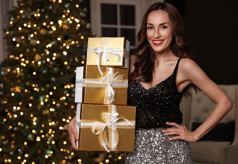 Beautiful woman with gift boxes in room. Christmas celebration. Beautiful woman with gift boxes in decorated room. Christmas celebration royalty free stock images