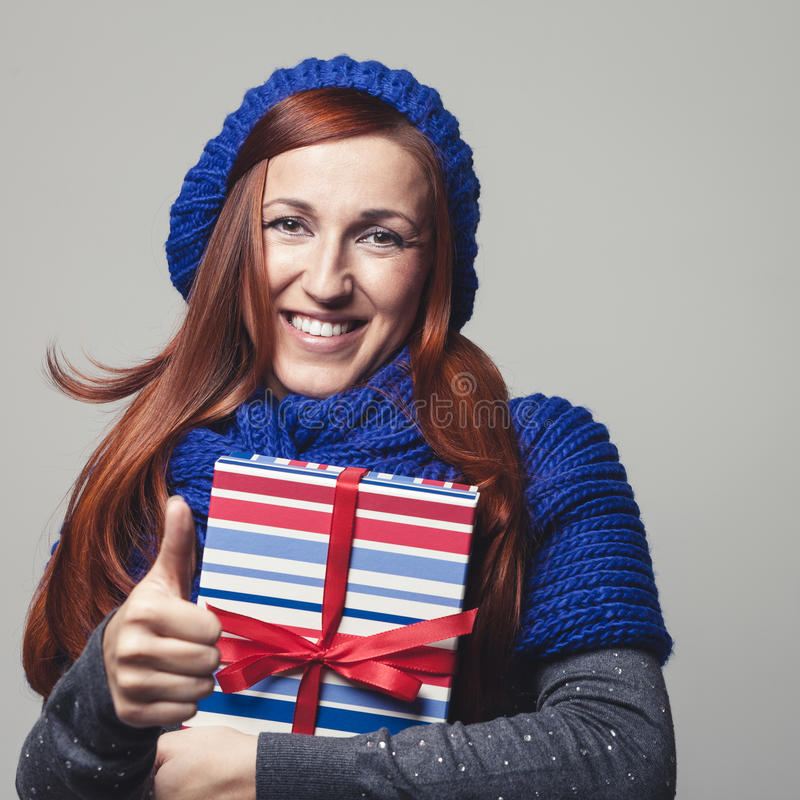 Beautiful woman with a gift giving a thumbs up royalty free stock image