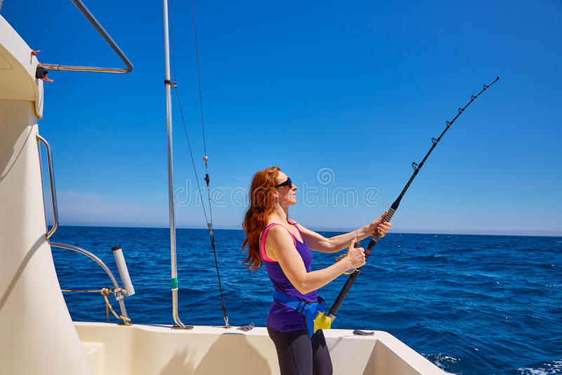 Beautiful woman girl fishing rod trolling in boat royalty free stock images