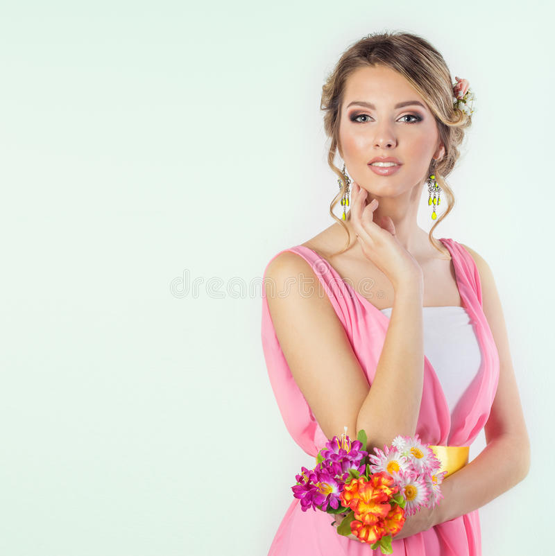 Beautiful woman girl like a bride with bright makeup hairstyle with flowers roses in the head in a pink dress. Beautiful woman girl like a bride with bright royalty free stock photos