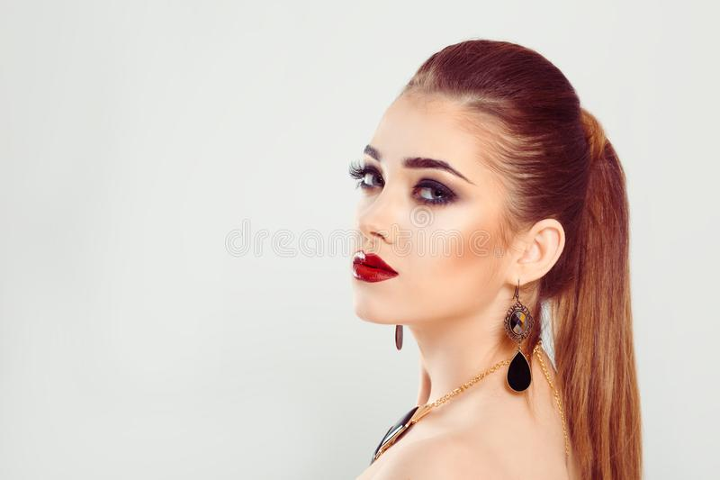 Model hair in ponytail woman is leaning against a white gray background stock photos