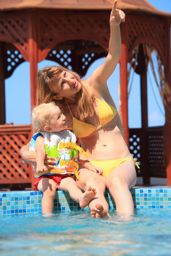 Beautiful woman with girl sitting on ledge pool