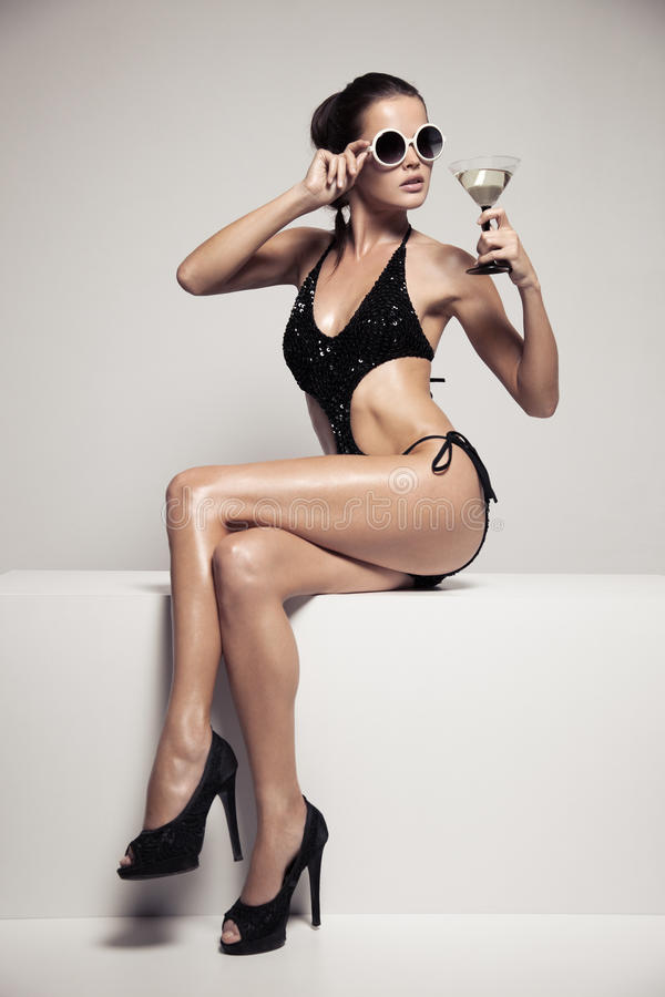 Beautiful woman with glamour make up in stylish black swimwear. Drink glass cocktail. royalty free stock photo