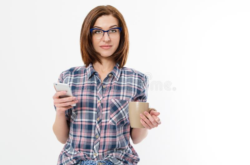 Beautiful woman with glasses holding mug smartphone. Young lady drinking tea and using gadget. Break concept. Isolated side view. On white background stock photography