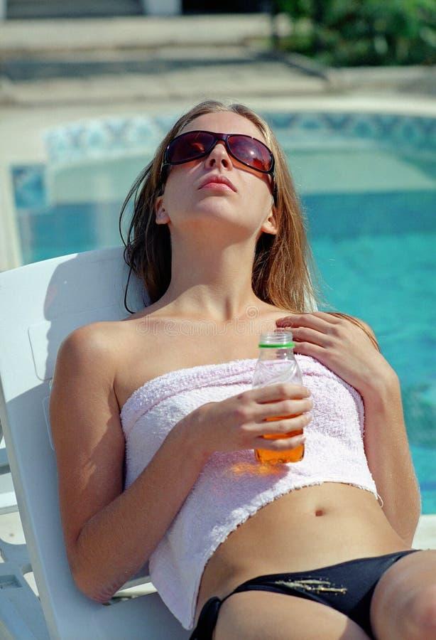 Beautiful woman in glasses before water pool