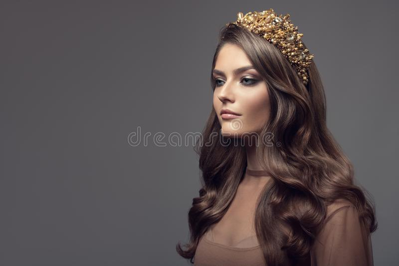 Beautiful woman in gold crown on her head. Long wavy brown hair stock images