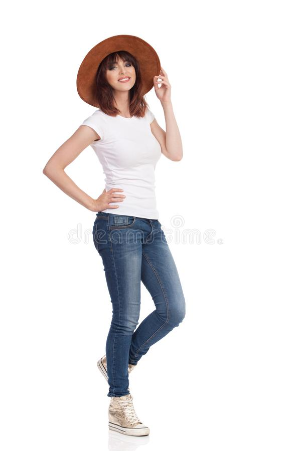 Beautiful Woman In Gold Sneakers And Brown Hat Is Standing With Hand On Hip royalty free stock images