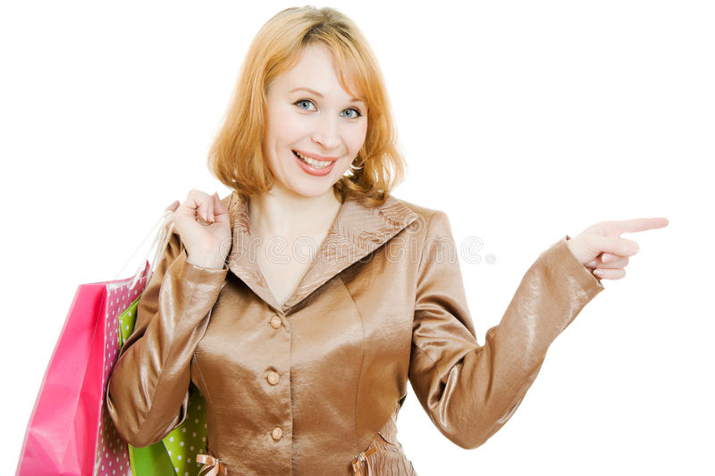 A beautiful woman in a gold suit with shopping. Points his finger on a white background royalty free stock images