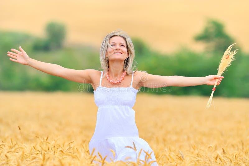 Beautiful woman in golden wheat field royalty free stock photo