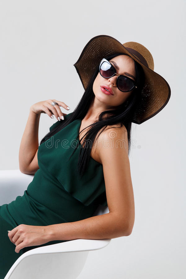 Beautiful woman in green dress. And hat on gray background empty stock photography