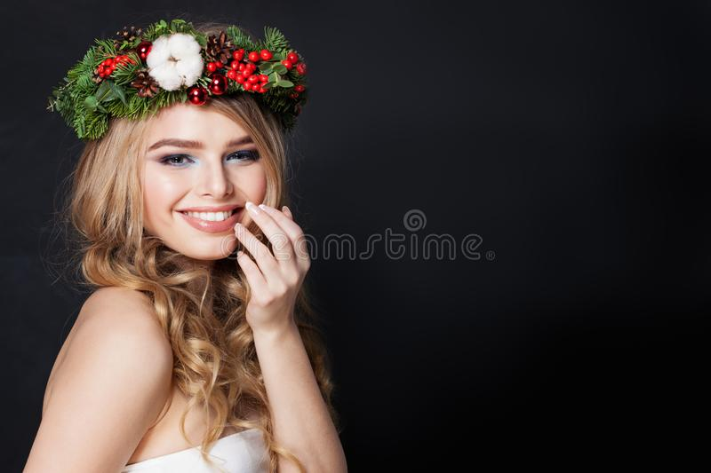 Beautiful woman in green fir crown on dark background. Happy girl with blonde hair and Xmas wreath royalty free stock images
