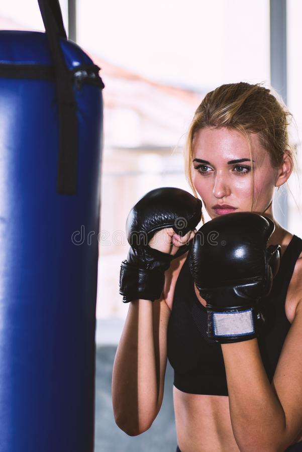 A beautiful woman guarding and punching on a sand bag stock photos