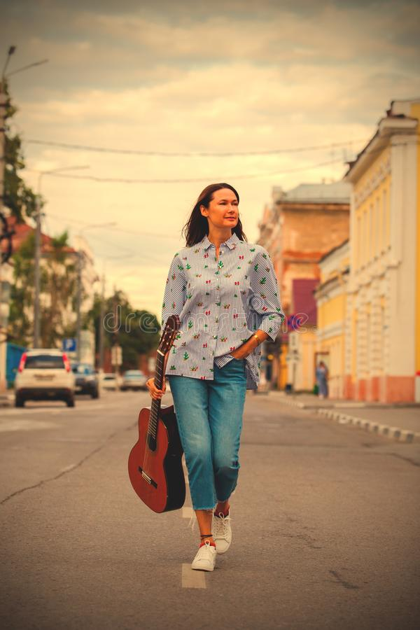 Beautiful woman with a guitar walking down the street royalty free stock photos