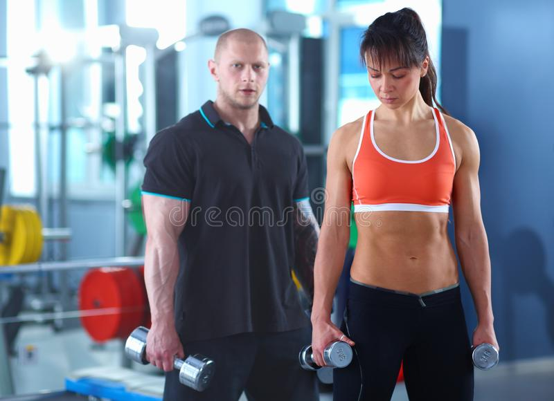 Beautiful woman at the gym exercising with her trainer . Beautiful woman. royalty free stock images