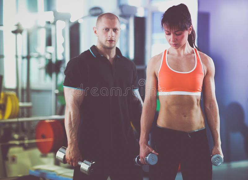 Beautiful woman at the gym exercising with her trainer . Beautiful woman. royalty free stock photos