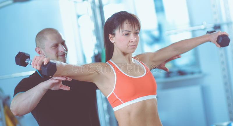 Beautiful woman at the gym exercising with her trainer . Beautiful woman. royalty free stock image