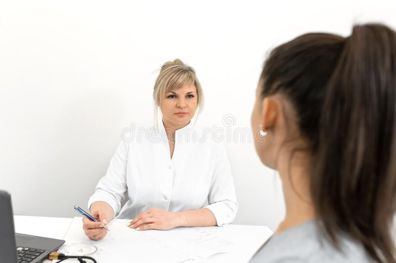 Beautiful woman gynecologist is conducting a reception with a young girl. Consultations and help gynecologist stock image