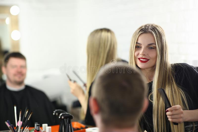 Beautiful Woman Hairdresser Styling Male Haircut. Barber Girl Making Hairdo for Man Client. Hairstyle for Customer in Beauty Studio. Professional Beautician royalty free stock images