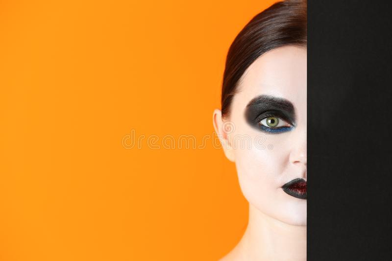 Beautiful woman with Halloween makeup and poster on color background stock photography
