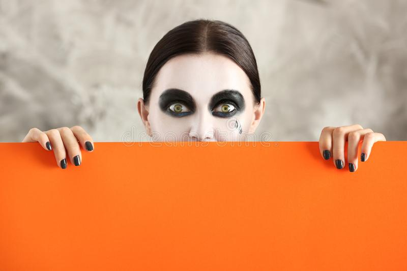 Beautiful woman with Halloween makeup and poster on grey background stock image