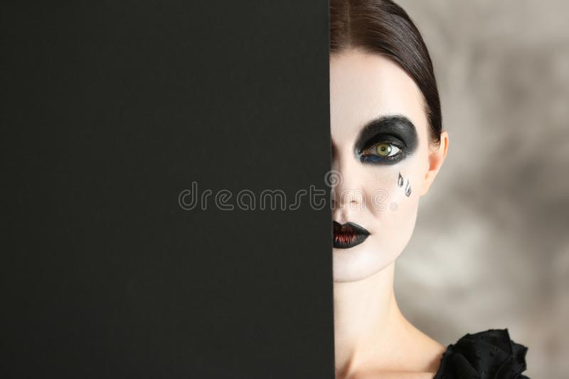 Beautiful woman with Halloween makeup and poster on grey background royalty free stock photography