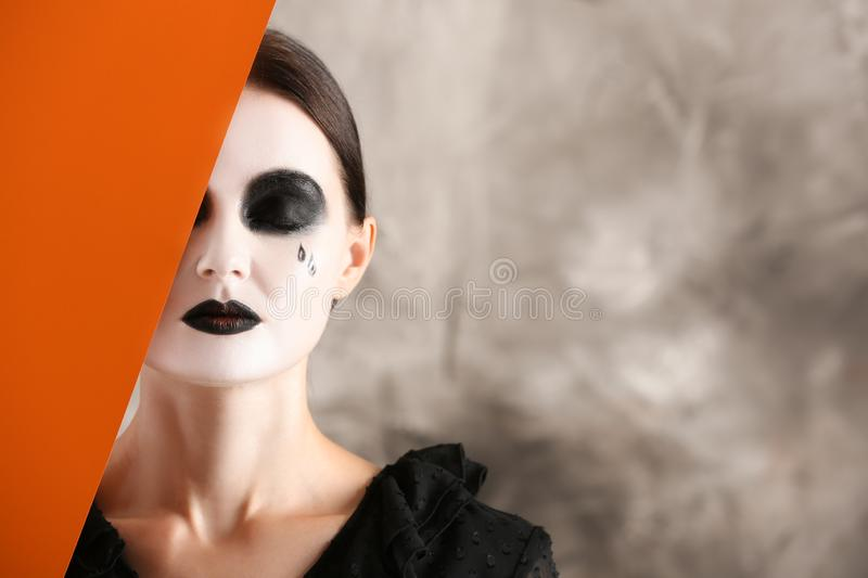 Beautiful woman with Halloween makeup and poster on grey background royalty free stock photo