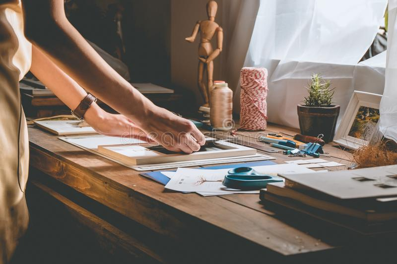 Beautiful woman hand crafting book at the tabletop with stationery. Stylish craftswoman with stationery work at his hipster workstation royalty free stock image