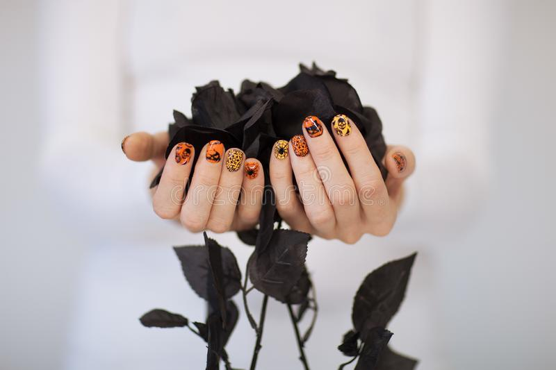Beautiful woman hands with cute halloween nail polish holding black roses stock photography