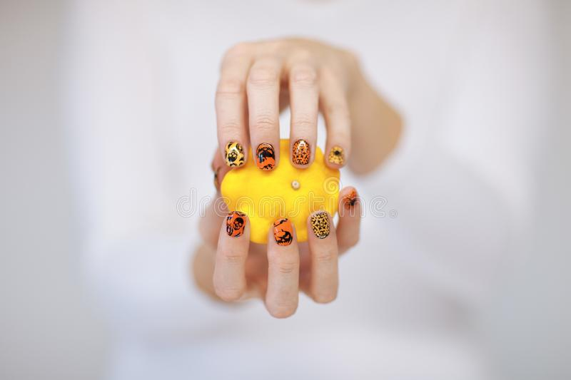 Beautiful woman hands with cute halloween nail polish holding little pumpkin stock image