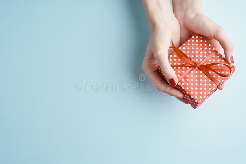 Woman hands holding red gift with ribbon, manicured hands with nail polish on aquamarine background with copy space royalty free stock photography