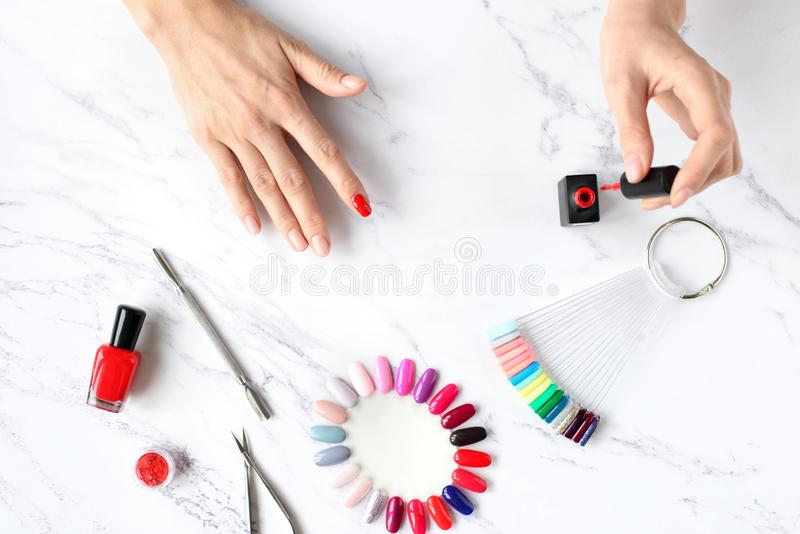 Beautiful woman hands painting nails with red nail polish on marble table with manicure set on it, top view stock photography