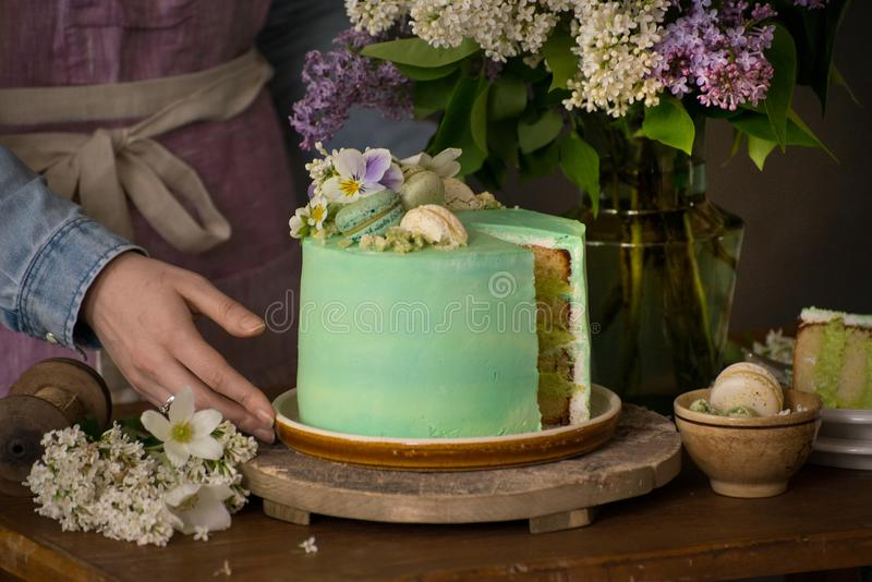 Beautiful woman hands with peace of beautiful green cake and flo stock photography