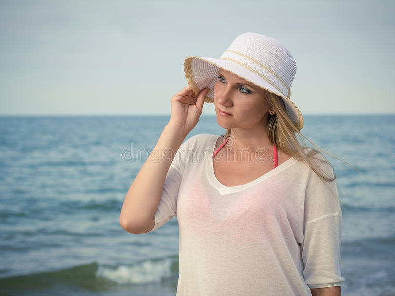Beautiful woman in hat against the evening sea. stock photo