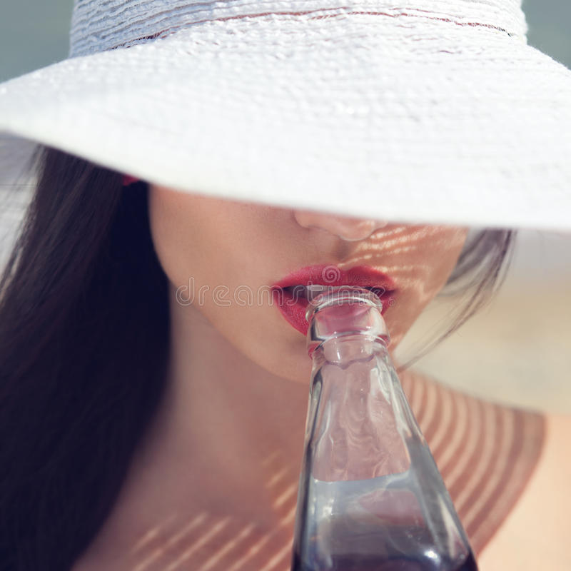Beautiful woman in hat drinking stock image