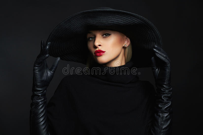 Beautiful woman in hat and leather gloves.halloween witch royalty free stock image