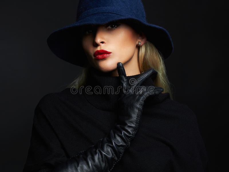 Beautiful woman in hat and leather gloves. Retro fashion girl. On the black background stock photo