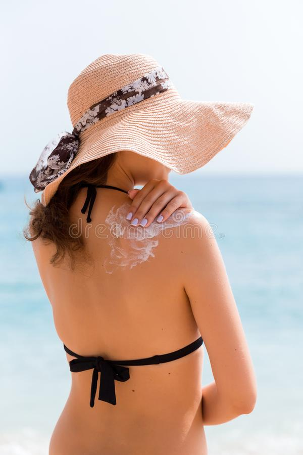 Beautiful woman in hat is putting sun cream on her shoulder at the beach.  royalty free stock image